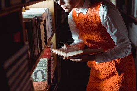 Foto de Vista recortada de la mujer en vestido naranja sosteniendo libro en la biblioteca - Imagen libre de derechos