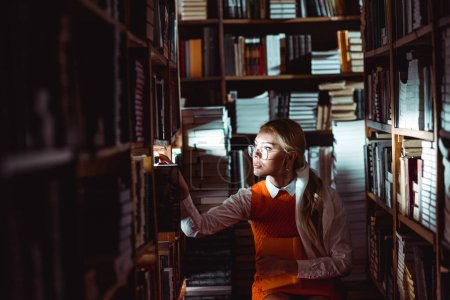 Photo for Beautiful and blonde woman in glasses and orange dress looking away in library - Royalty Free Image
