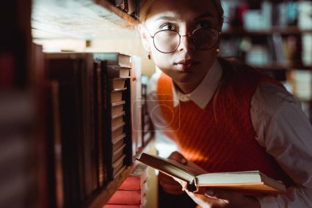 Photo for Beautiful woman in glasses holding book and looking away in library - Royalty Free Image