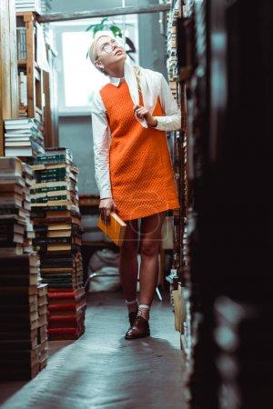 Foto de Hermosa y rubia mujer en gafas y vestido naranja sosteniendo libro y mirando hacia arriba en la biblioteca - Imagen libre de derechos