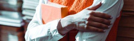 Foto de Disparo panorámico de la mujer con los brazos cruzados sosteniendo libro en la biblioteca - Imagen libre de derechos