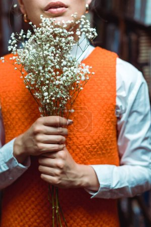 Photo for Cropped view of woman in orange dress holding white flowers - Royalty Free Image
