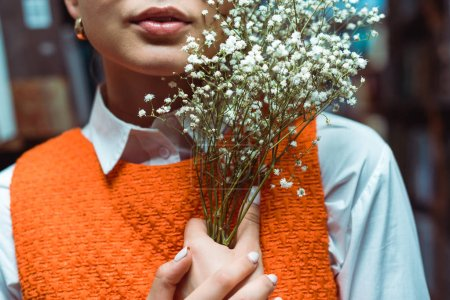 Photo for Cropped view of young adult woman holding white flowers - Royalty Free Image