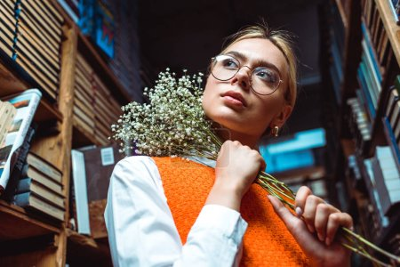 Photo for Low angle view of woman in glasses holding white flowers and looking away in library - Royalty Free Image