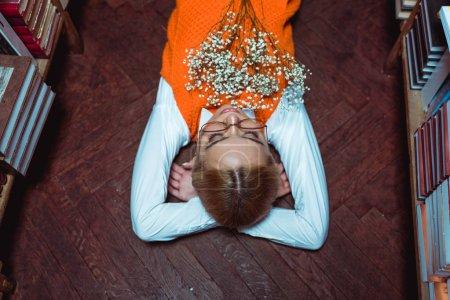 Foto de Vista de ángulo alto de la hermosa mujer acostada en el suelo de madera con flores blancas en la biblioteca - Imagen libre de derechos