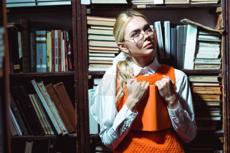 Foto de Rubia y pensativa mujer sosteniendo libro y mirando hacia otro lado en la biblioteca - Imagen libre de derechos