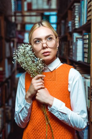 Photo for Blonde and pensive woman holding white flowers and looking away in library - Royalty Free Image