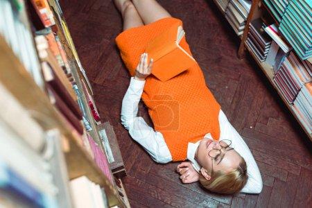 Foto de Vista de ángulo alto de la hermosa mujer con vestido naranja acostado en el suelo y sosteniendo el libro en la biblioteca - Imagen libre de derechos