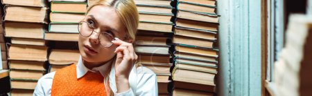 Photo for Panoramic shot of blonde and attractive woman in glasses looking away in library - Royalty Free Image