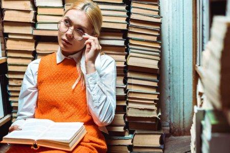 Foto de Rubia y atractiva mujer en gafas sosteniendo libro y mirando hacia otro lado en la biblioteca - Imagen libre de derechos