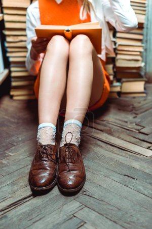 Photo for Cropped view of woman sitiing on wooden floor with book in library - Royalty Free Image
