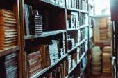 """Постер, картина, фотообои """"селективное внимание ретро-книг на деревянных полках в библиотеке"""""""