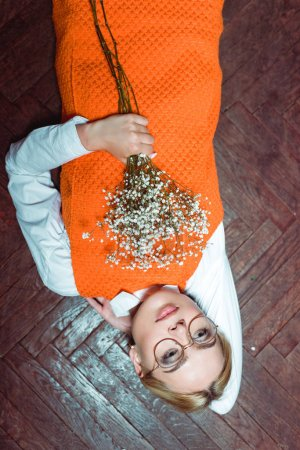 Photo for Top view of beautiful woman lying on wooden floor and holding white flowers - Royalty Free Image