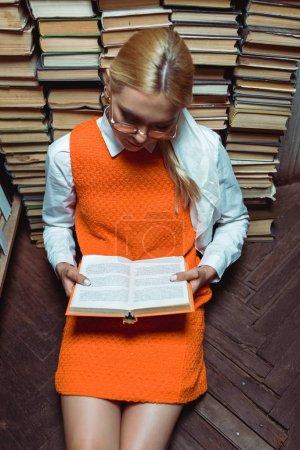 Photo pour Vue grand angle de belle femme assise sur le sol et le livre de lecture dans la bibliothèque - image libre de droit