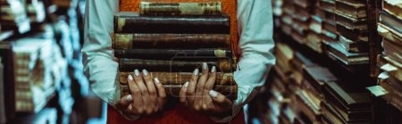 Photo for Panoramic shot of woman holding retro books in library - Royalty Free Image