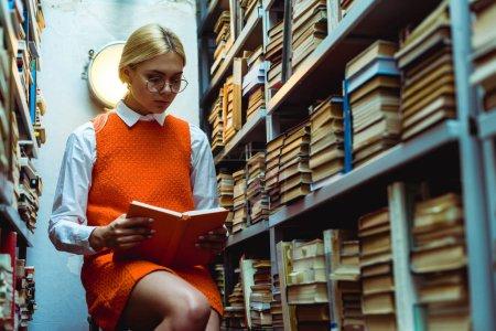 mujer hermosa y rubia en vestido naranja y gafas libro de lectura en la biblioteca
