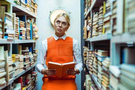 Photo pour Belle et pensive femme dans le livre de fixation de robe orange et regardant vers le haut dans la bibliothèque - image libre de droit