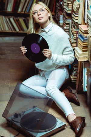 Photo for Pretty and blonde woman sitting on floor and holding vinyl in library - Royalty Free Image