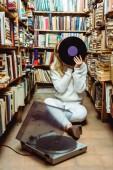 """Постер, картина, фотообои """"блондинка в белом свитере сидит на полу и проведение винила в библиотеке"""""""