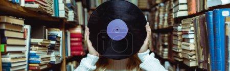 Foto de Foto panorámica de la joven mujer adulta sosteniendo vinilo en la biblioteca - Imagen libre de derechos