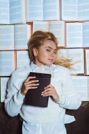 Foto de Mujer atractiva y rubia con los ojos cerrados acostados y sosteniendo el libro - Imagen libre de derechos