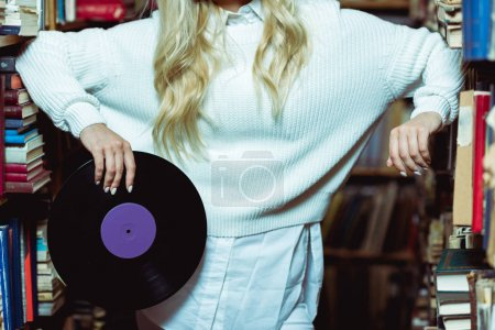 Photo for Partial view of young adult woman holding vinyl in library - Royalty Free Image