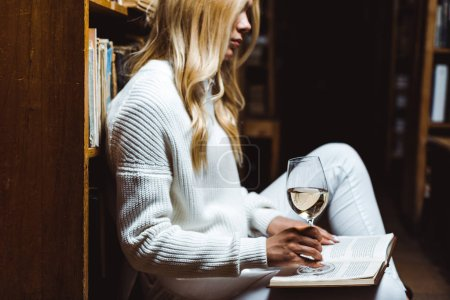Photo for Side view of blonde woman reading book and holding glass wine in library - Royalty Free Image