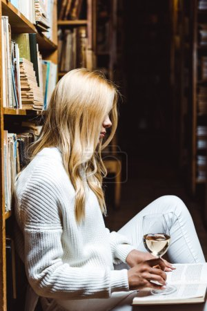Photo for Side view of blonde woman reading book and holding wine glass in library - Royalty Free Image