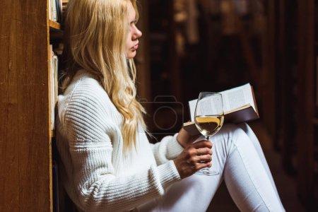 Photo pour Vue latérale de blonde et jolie femme lisant le livre et tenant le verre à vin dans la bibliothèque - image libre de droit
