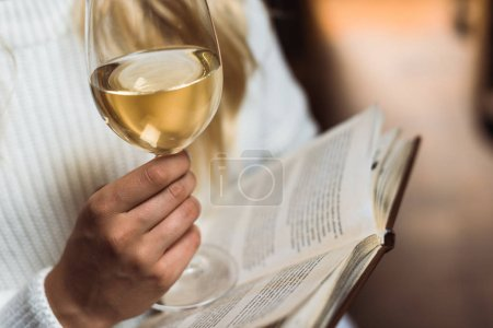 Photo for Cropped view of young adult woman holding wine glass and book - Royalty Free Image