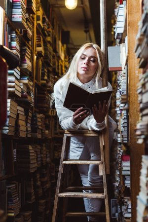 Photo for Blonde and pretty woman in white sweater reading book in library - Royalty Free Image