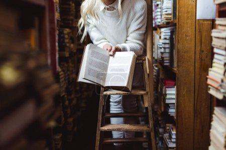 Photo pour Vue recadrée de la femme en pull blanc tenant livre dans la bibliothèque - image libre de droit