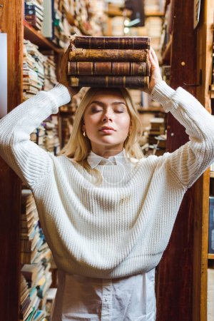 Photo for Blonde and pretty woman in white sweater with closed eyes holding books in library - Royalty Free Image