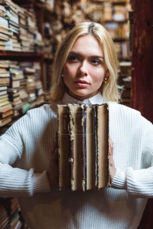 Photo for Blonde and pretty woman holding books and looking away in library - Royalty Free Image