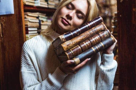 Photo for Blonde and pretty woman with closed eyes holding books in library - Royalty Free Image