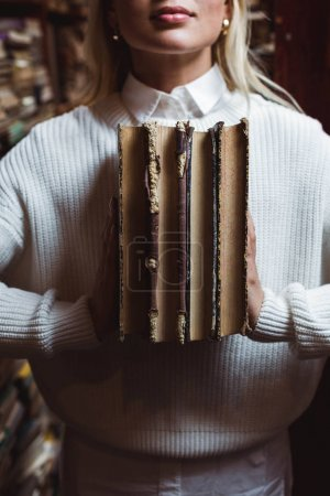 Photo for Cropped view of woman in white sweater holding retro books in library - Royalty Free Image