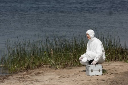 water inspector in protective costume with inspection kit sitting on river coast