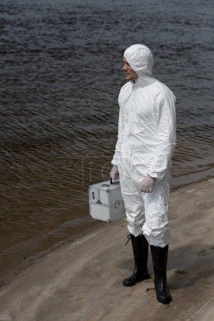 Photo pour Vue pleine longueur de l'inspecteur de l'eau dans la trousse d'inspection de fixation de costume de protection et restant sur la côte de fleuve - image libre de droit
