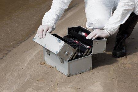 Photo pour Vue raccourcie de l'inspecteur d'eau dans le kit d'ouverture de gants de latex avec des tubes à essai sur la côte sablonneuse - image libre de droit