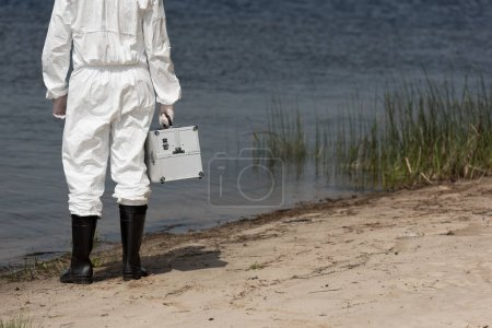 cropped view of water inspector in protective suit holding inspection kit on river coast