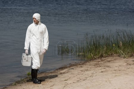 full length view of water inspector in protective suit holding inspection kit and standing on river coast
