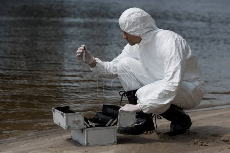 water inspector in latex gloves and protective costume opening inspection kit on sandy coast