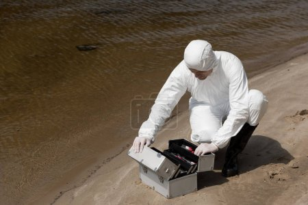Foto de Water inspector in latex gloves and protective costume opening inspection kit on sandy coast - Imagen libre de derechos