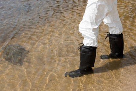 Photo pour Vue raccourcie de l'inspecteur d'eau dans le costume protecteur et les bottes restant dans la rivière - image libre de droit