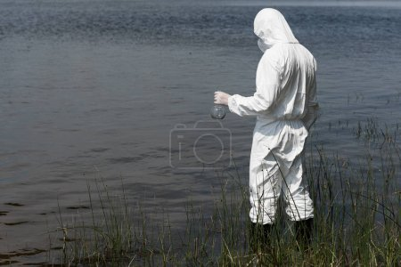Photo pour Water inspector in protective costume holding flask while standing near river - image libre de droit
