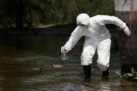 Photo for Water inspector in protective costume, respirator and goggles holding flask with water sample - Royalty Free Image