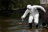 """Постер, картина, фотообои """"водный инспектор в защитном костюме, респираторе и очках, держащих колбу с образцом воды"""""""