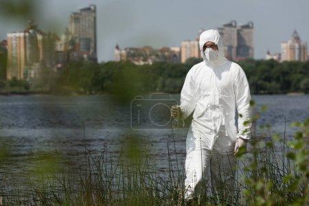 Photo pour Mise au point sélective de l'inspecteur de l'eau dans le costume protecteur, le respirateur et les lunettes retenant le flacon avec l'échantillon d'eau - image libre de droit