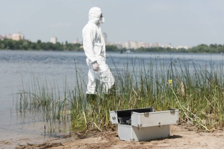 Photo for Selective focus of water inspector in protective costume and inspection kit on foreground - Royalty Free Image
