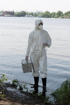 full length view of water inspector in protective costume holding inspection kit and flask at river